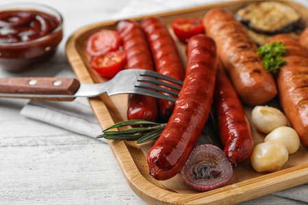 Delicious grilled sausages on white wooden table, closeup. Barbecue food