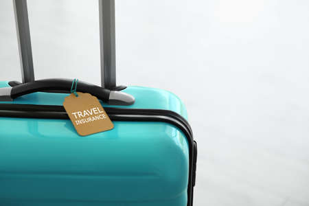 Stylish suitcase with travel insurance label on light background, closeup. Space for text