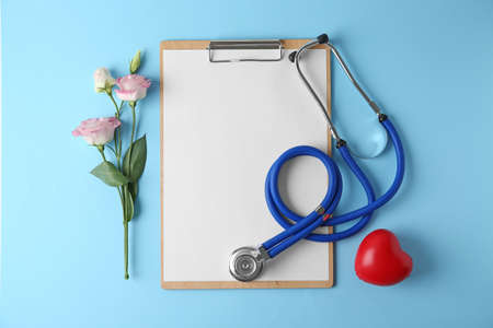 Flat lay composition with stethoscope and flowers on light blue background, space for text. World health day