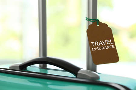 Stylish suitcase with travel insurance label on blurred background, closeup. Space for text
