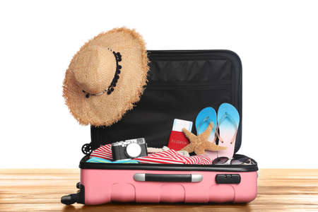 Open pink suitcase with different beach objects on wooden table, white background