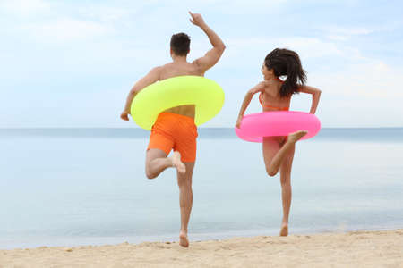 Happy young couple having fun with inflatable rings on beach near sea