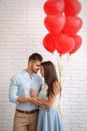 Young couple with air balloons near white brick wall. Celebration of Saint Valentines Day