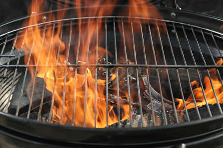 New modern barbecue grill with burning firewood, closeup