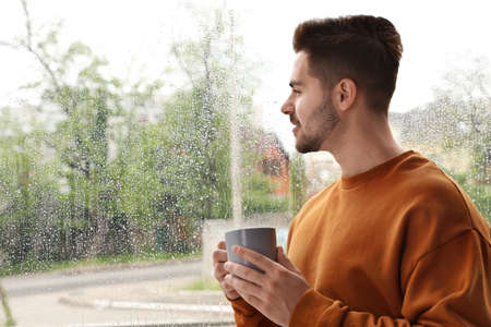 Happy handsome man with cup of coffee near window on rainy day