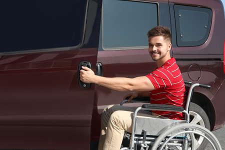 Young man in wheelchair opening door of his van outdoors Stock Photo