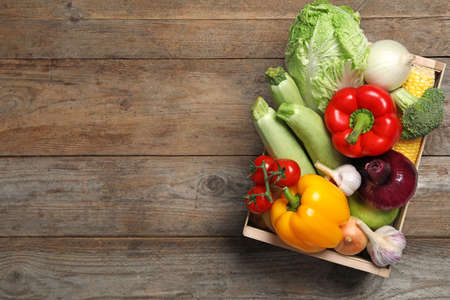 Fresh vegetables in crate on wooden background, top view. Space for text