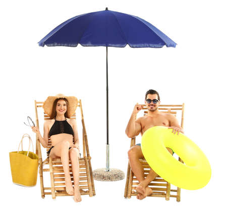 Young couple with beach accessories on sun loungers against white background