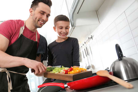 Dad and son cooking together in kitchen