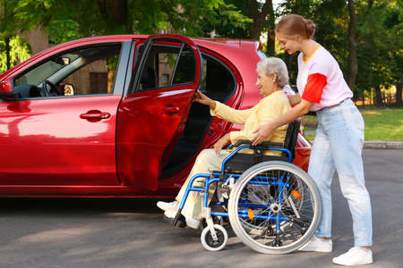 Young woman helping disabled grandmother in wheelchair to get into car outdoors
