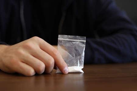 Criminal holding drug at wooden table, closeup