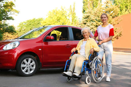 Senior woman in wheelchair with granddaughter near car outdoors Stock Photo
