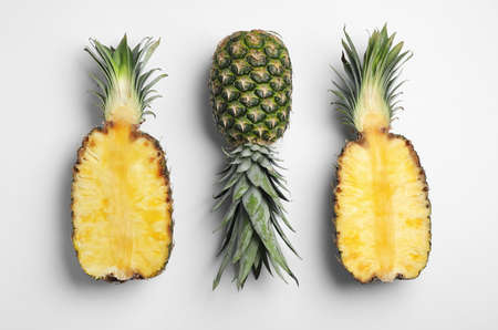 Tasty ripe pineapples on white background, top view