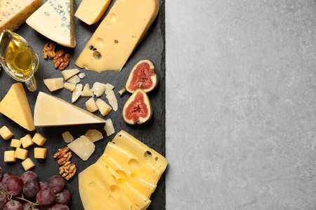 Different delicious cheeses served on grey table, top view. Space for text Фото со стока