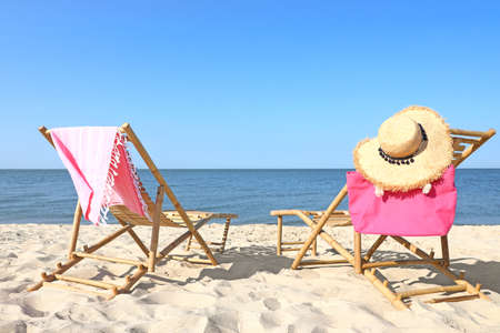 Empty wooden sunbeds and beach accessories on sandy shore