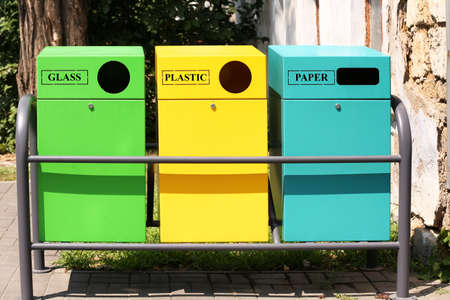 Waste sorting bins on city street. Recycling concept