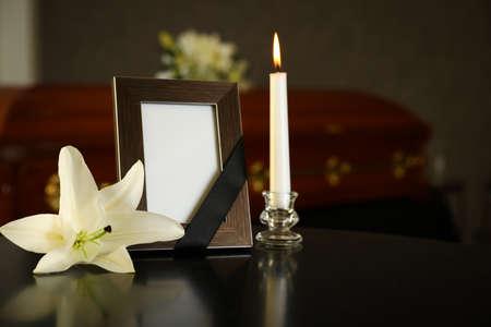 Schwarzer Bilderrahmen mit brennender Kerze und weißer Lilie auf dem Tisch im Bestattungsinstitut