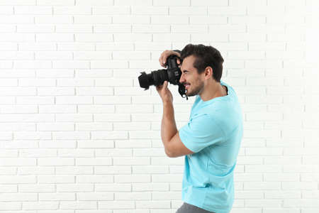 Young professional photographer taking picture near brick wall. Space for text Imagens