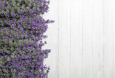 Beautiful tender lavender flowers on white wooden table, top view. Space for text