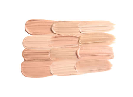 Samples of different foundation shades on white background, top view