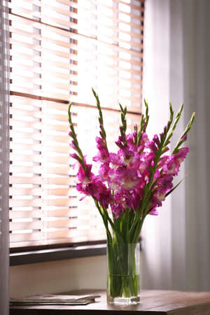Vase with beautiful pink gladiolus flowers on wooden table in room, space for text Stock fotó