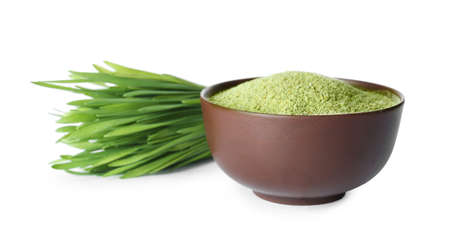 Fresh wheat grass and bowl with powder on white background