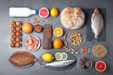 Flat lay composition with different products on dark grey background. Food allergy concept