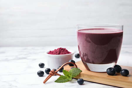 Tasty acai drink, powder and berries on marble table. Space for text