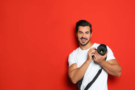 Young photographer with professional camera on red background. Space for text Stock Photo
