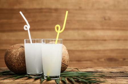 Composición con vasos de agua de coco sobre fondo de madera. Espacio para texto