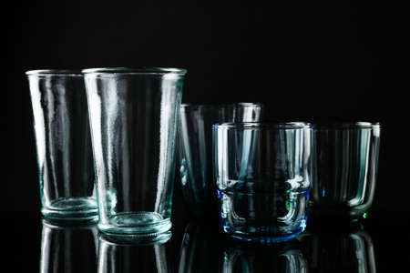 Set of different colorful empty glasses on black background 스톡 콘텐츠