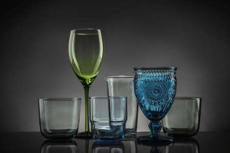 Set of different colorful empty glasses on table against grey background