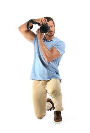 Young professional photographer taking picture on white background Foto de archivo