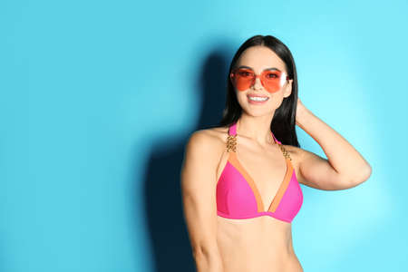 Beautiful young woman in stylish bikini with sunglasses on light blue background. Space for text Imagens