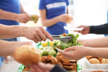 Volunteers serving food to poor people, closeup Banco de Imagens