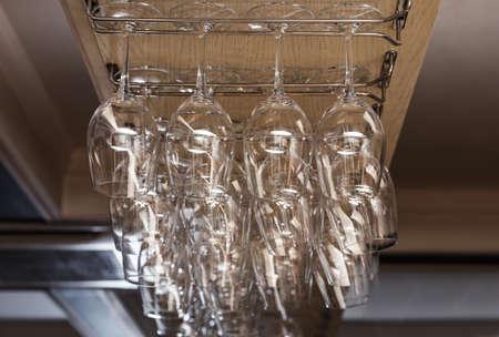 Set of empty clean glasses on bar racks 스톡 콘텐츠