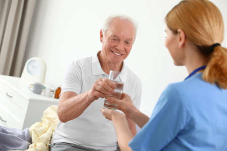 Nurse giving glass of water to elderly man indoors. Medical assistance Stock Photo