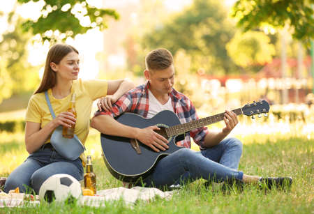 Young couple enjoying picnic in park on summer day