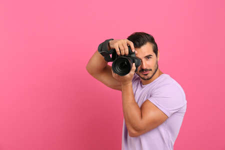 Young professional photographer taking picture on pink background. Space for text Stock Photo