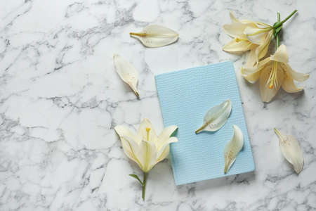 Beautiful lilies with notebook on marble background, top view. Space for text