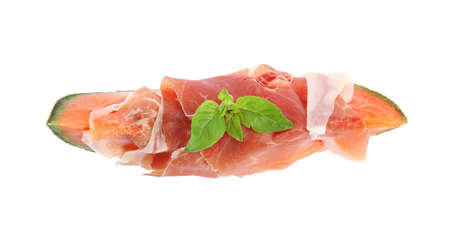 Slice of fresh melon with prosciutto and basil on white background, top view