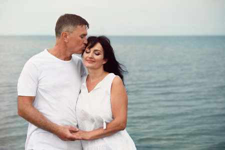 Happy mature couple spending time together on sea beach. Space for text Stock Photo