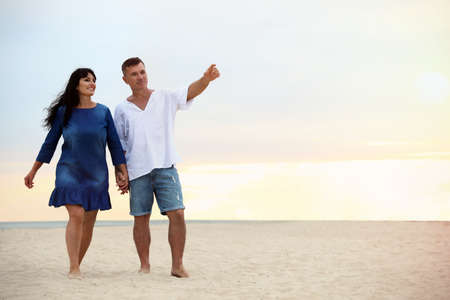 Happy mature couple walking together on sea beach at sunset. Space for text