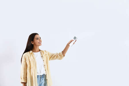 Young woman turning on air conditioner against white background