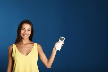 Young woman with air conditioner remote on blue background. Space for text