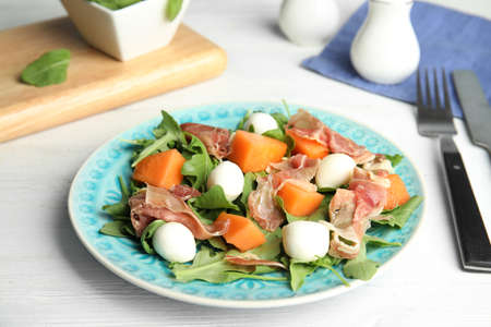 Fresh melon with prosciutto, mozzarella and arugula on white wooden table Standard-Bild