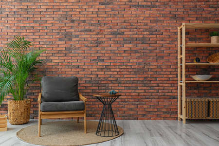 Modern room interior with stylish grey armchair and potted plant near brick wall