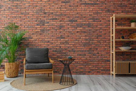 Modernes Zimmerinterieur mit stilvollem grauem Sessel und Topfpflanze in der Nähe der Backsteinmauer