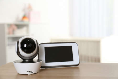 Baby monitor with camera on table in room. Video nanny