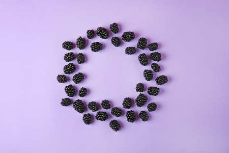Frame made of tasty blackberries on purple background, top view with space for text Stock Photo